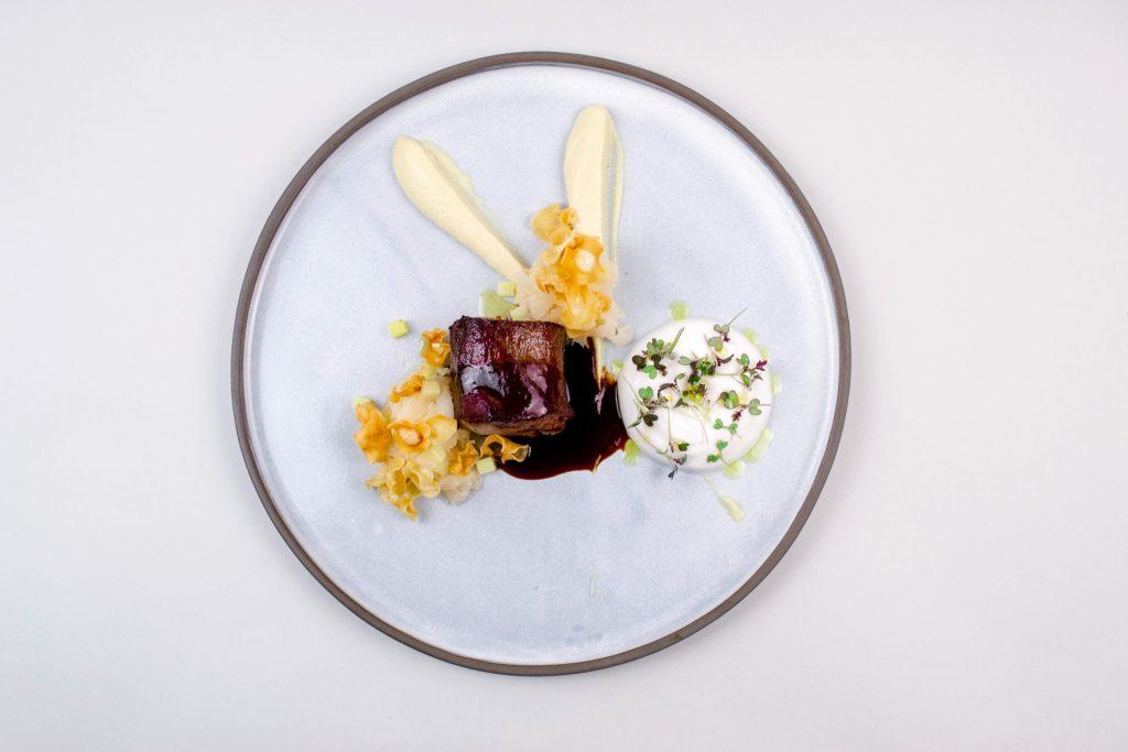 Sedem TR2020j Hrbet divje svinje, sotirana repa s krompirjem, pena kisle repe, pastinakov pire, čips pastinaka, divjačinska omaka
